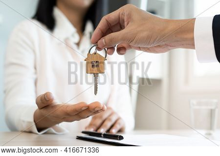 A New Homeowner Accepts A House Key From A Real Estate Agent After Agreeing To A Successful Buy-home