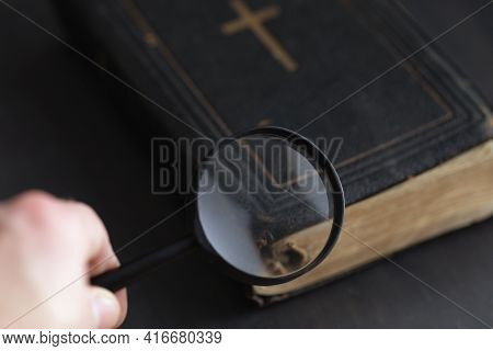 Closed Ancient Bible With Gold Cross With Hand Holding Magnifying Glass. Search For Truth And Meanin
