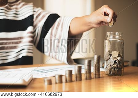 Woman's Hand. Put A Coin Into A Glass Bottle With Coins, Saving Money With Coins, Stepping Into A Su