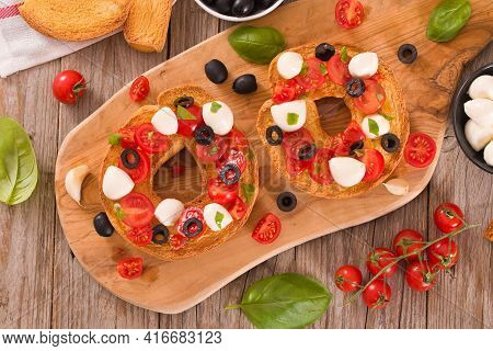 Friselle With Tomatoes And Mozzarella Cheese On Cutting Board.