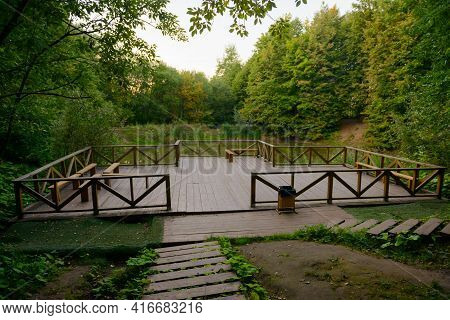 A Small Observation Deck Made Of Wood In The Middle Of The Forest With A Pond On A Summer Evening