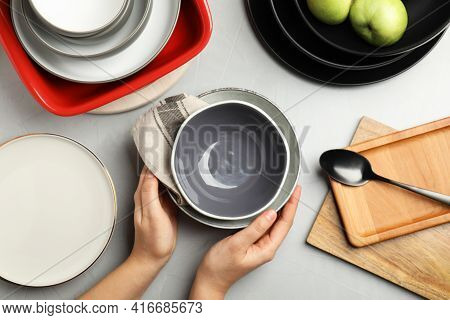 Woman With Clean Dishware At Grey Table, Top View
