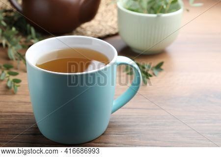 Cup Of Aromatic Eucalyptus Tea On Wooden Table, Closeup. Space For Text