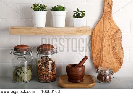 Wooden Dishware And Different Products On Grey Table Near White Brick Wall In Kitchen