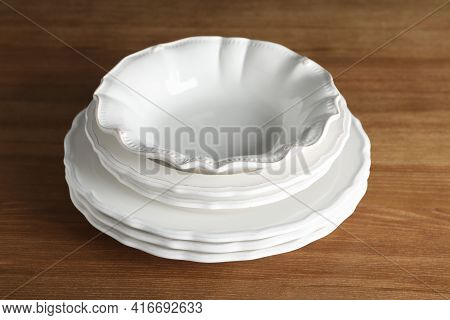 Stack Of Ceramic Dishware On Wooden Table, Closeup