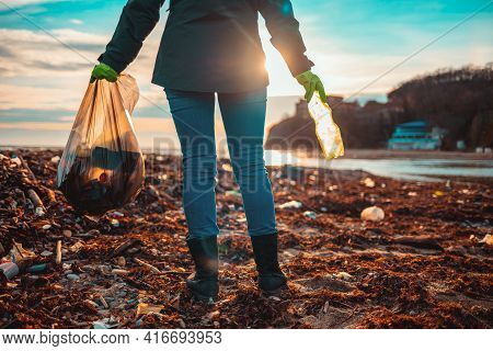 Day Of Earth. A Female Volunteer Stands On A Muddy Beach With A Bag Of Garbage. Rear View.