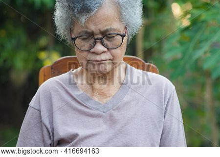 Elderly Woman With Short White Hair, Wearing Glasses, Eye Closed And Sitting On Chair In The Garden.