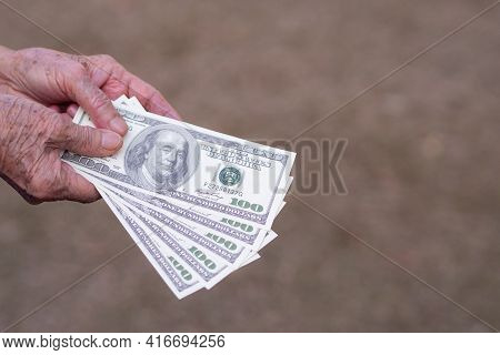 Close-up Of Elderly Woman Hands Holding $100 Amount Of $500 Dollars. Selective Focus. Space For Text