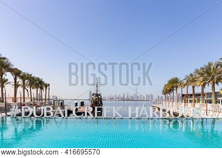 Dubai, Uae, 22.02.2021. Dubai Creek Harbour Sign By Turquoise Water Pool With Rows Of Palm Trees, Bl