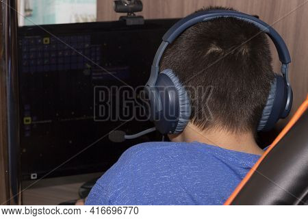 The Back Of The Head Of A Teenager In Blue Headphones Behind The Monitor. A Boy In Headphones Studie