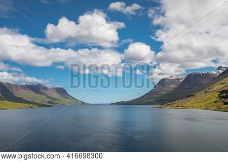 Ocean Fjord Of Seydisfjordur, Iceland, On A Warm, Partly Cloudy Day. Steep Green Hills Next To The A