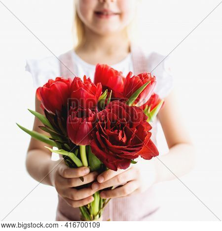 Small Smiling Girl Holding Bouquet Of Red Tulip Flowers. Concept For Greeting Card For Easter, Mothe