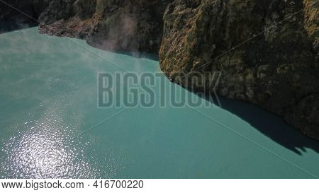 Flight Over The Vulanice Lakes At A Low Altitude. Close Up View Of A Rock Wall Separating Colorful L