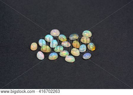 Natyral Ethiopian Opal Small Cabochons Lot On Black Background. White Opaque Stone Base With Multico