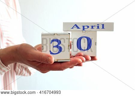 Calendar For April 30 : Women's Hands Hold Cubes With The Number 30, The Name Of The Month Of April