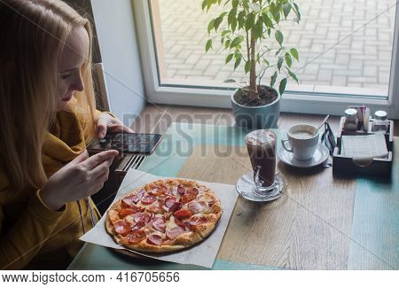 A Blogger Girl Sits In A Cafe And Shoots A Pizza On A Smartphone. Work In Social Networks, Video Blo