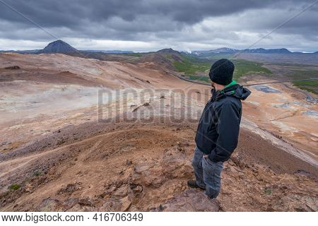 A Man Overlooking Volcanic Icelandic Landscape From The Top Of Namafjall. Dramatic Clouds In The Sky