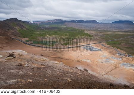 Volcanic Icelandic Landscape From The Top Of Namafjall. Dramatic Clouds In The Sky. Road In The Dist