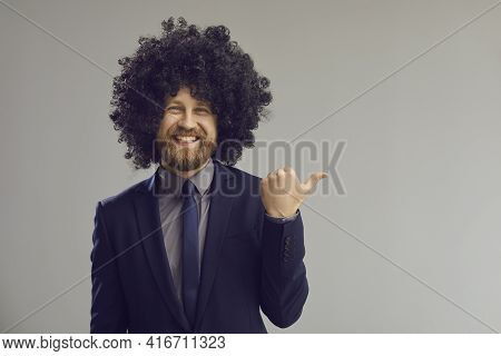 Funky Business Man In Hair Wig Pointing With Thumbs Up At Grey Copy Space