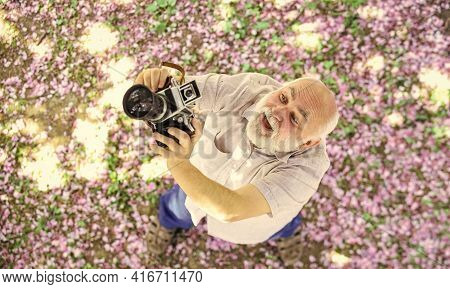 Photography Hunt. Old Happy Man Looking Upwards At Tree. Senior Man Holding Professional Camera. Edu