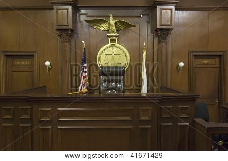 Empty courtroom with chair of judge and flags