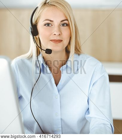 Blonde Business Woman Sitting And Communicated By Headset In Call Center Office. Concept Of Telesale