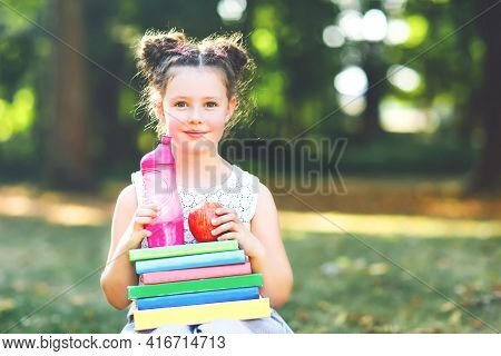 Happy Adorable Little Kid Girl Reading Book And Holding Different Colorful Books, Apples And Water B