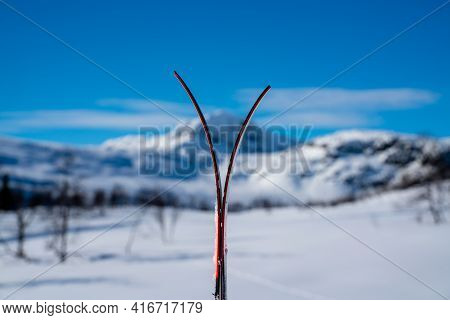 Skis Stacked Together In The Snow With Blurred Snow Capped Mountains.