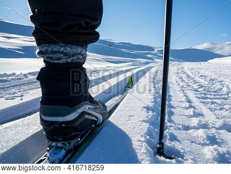 Cross Country Skiing Boot And Ski Gliding In A Slope Though The Mountains.
