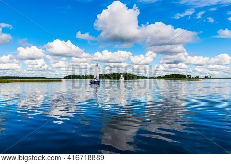 Sailing Yacht In The Lake With Gloomy Sky Before The Rain. Yacht Sailing On The Lake Against A Blue