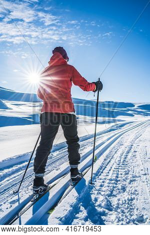 Young Woman Cross Country Skiing On A Sunny Day In Snow Covered Mountains.