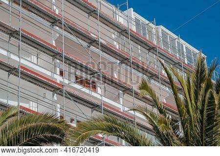 Extensive Scaffolding Providing Platforms For Safe Work. Renovation Of The Facade Of A Hotel In A Eu