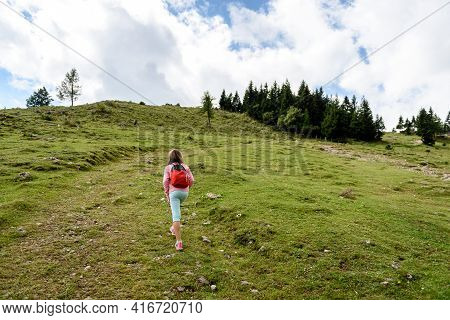 Children Hiking In Mountains Or Meadows With Sport Hiking Shoes. Girls Are Walking Through Mountain