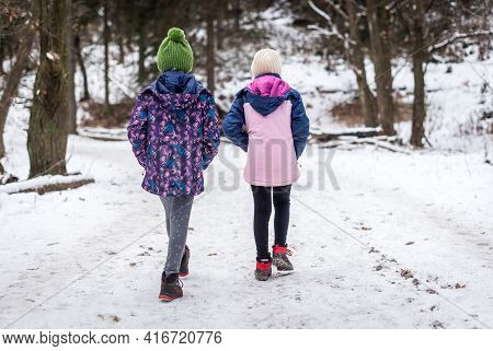 Children Hiking In Snow Mountains Forest On Family Trip.