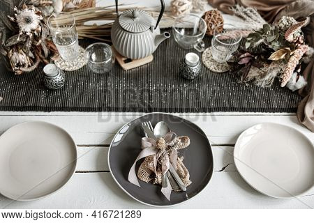Stylish Crockery And Cutlery On A Set Table In Coffee Colors With Scandinavian-style Decorative Elem
