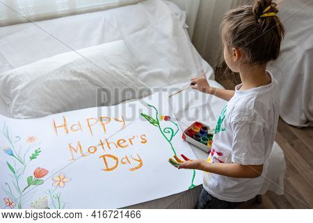 Little Girl Paints Greeting Card For Mom On Mother's Day With The Inscription Happy Mother's Day And