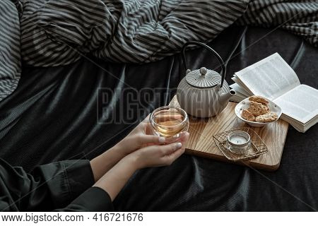 A Woman Has Breakfast In Bed With Tea And Cookies, Lying In Bed On A Day Off.