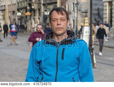 Street Portrait Of A 45-50-year-old Man With A Serious Expression On A Neutral Urban Background, Med