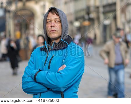 Street Portrait Of A 45-50-year-old Man With A Serious Expression In A Gray Hoodie On His Head On A