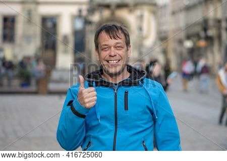 Street Portrait Of A 45-50-year-old Laughing Man With A Thumbs Up On A Blurry Urban Background, Ever