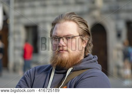 Street Portrait Of A Smiling Blond 25-30 Year Old Man With Glasses And A Beard On The Background Of