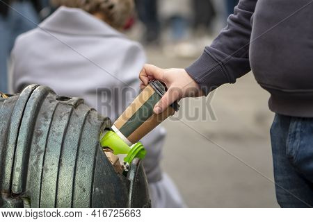 A Man\\\'s Hand Throws A Paper Coffee Cup Into A Street Trash Can, Close-up, Selective Focus. Concep