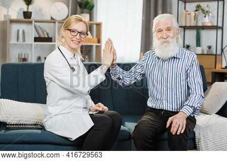Front View Of Positive Pleasant Female Doctor And Handsome Senior Bearded Man Patient, Giving High F