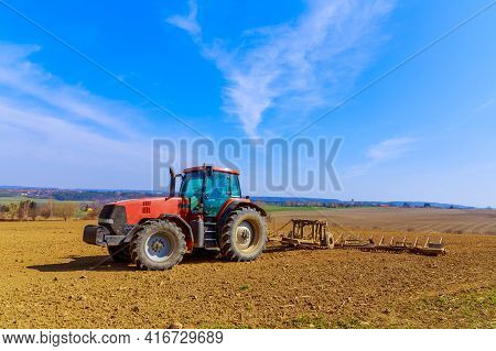 A Farmer Plows The Soil In The Field With A Chisel Plow On A Tractor. Red Agricultural Tractor With