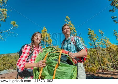 Camping couple summer tourist lifestyle happy young people unfolding tent bringing gear for camp holiday on forest nature outdoor landscape background.