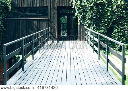 Wooden Bridge To The Green Building. Wooden Bridge With Handrails To The Building Entwined With Gree