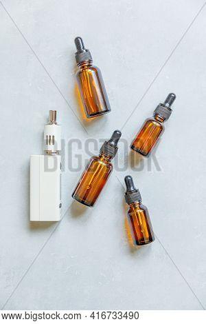Vaping Device E-cigarette Electronic Cigarette And Liquid Bottles On Concrete Stone Grey Background.