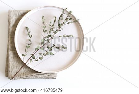 Closeup Of Green Eucalyptus Leaves Branches, Earthenware Plate And Gray Cotton Towel On White Table