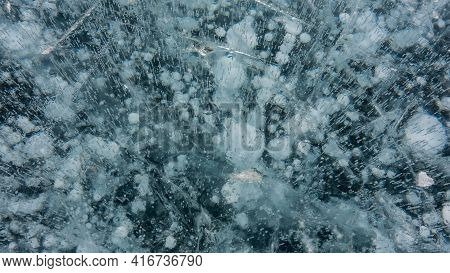 Transparent Ice Of Lake Baikal, Close-up. Cracks Are Visible On The Smooth Turquoise Surface, In The