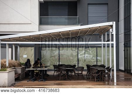 Belgrade, Serbia - April 3, 2021: Selective Blur On Three Girls Sitting  On Empty Terrace And Patio